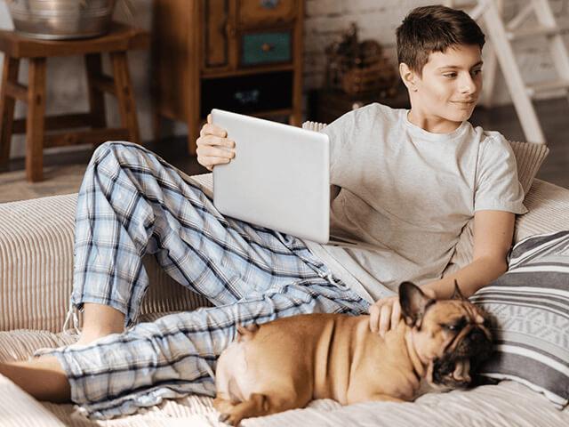 Garçon installé sur le canapé avec son chien