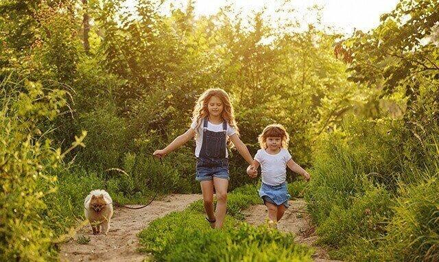 Des enfants qui promènent leur chien dehors