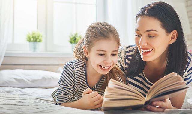 Une maman lisant un livre à sa fille dans un lit