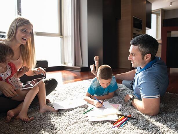 Une famille qui joue à des jeux de société à l'intérieur sur un tapis