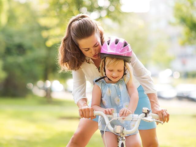 Une maman qui aide sa fille à faire du vélo