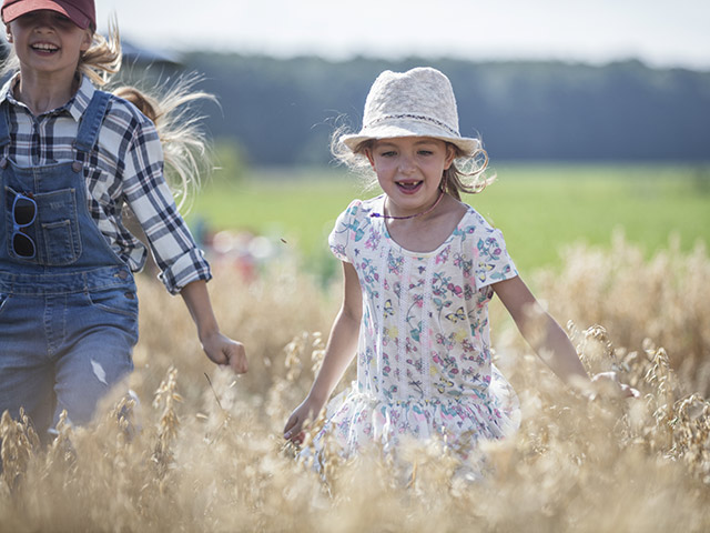 Sisters playing outside in tall grass