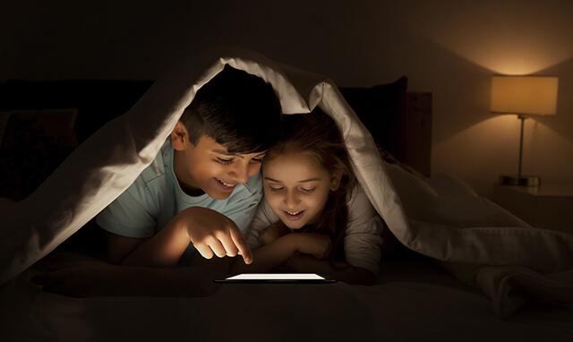 Des enfants installés dans un lit, dans le noir, et lisant sur une tablette