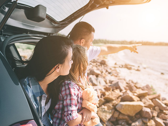 Family sitting in back of car on a beach