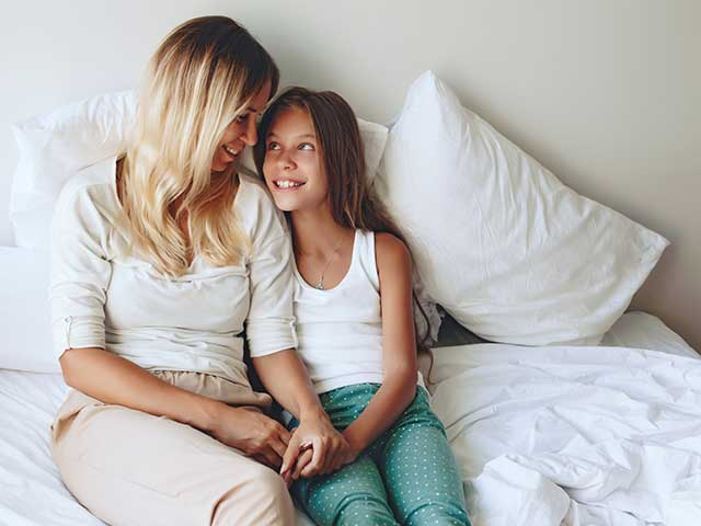Mother and daughter holding hands sitting up in a bed